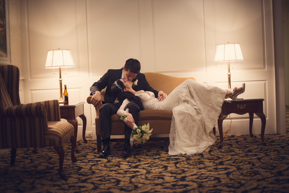 Bride and Groom kiss laying on couch THPHOTO