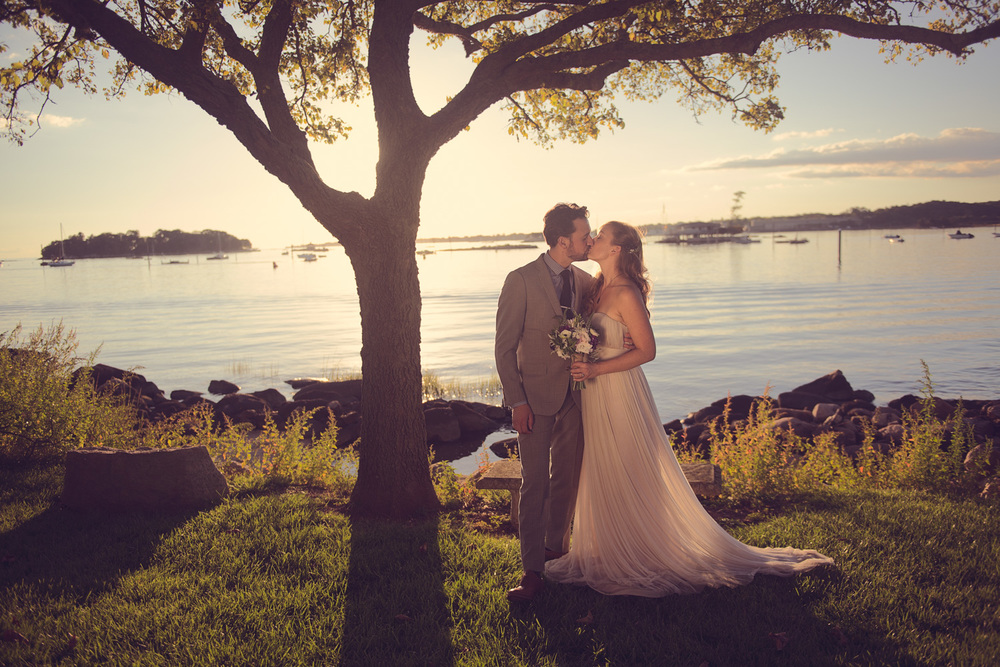 Bride and groom kiss on bench at sunset beneath tree Branford, CT THPHOTO