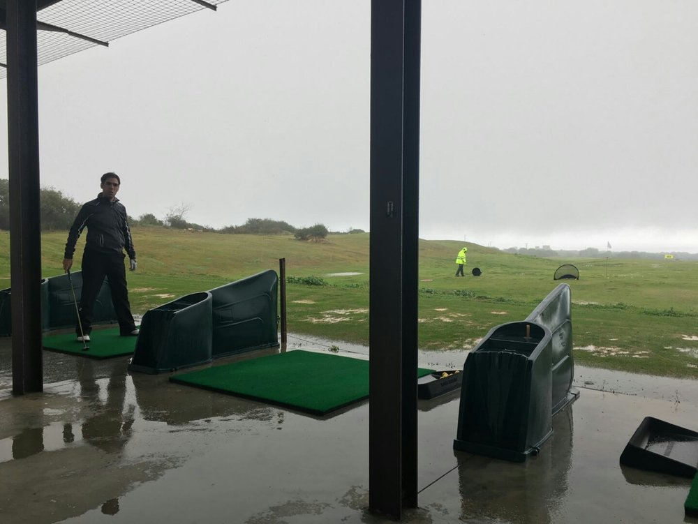 Trying to practice at Alcaidesa Golf Resort during the torrential rain!