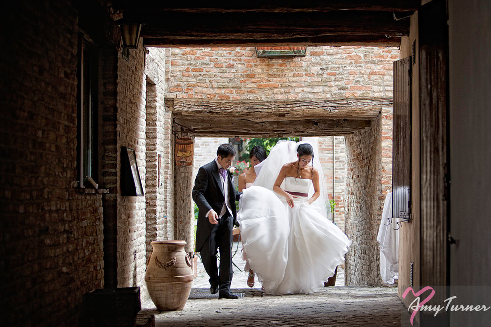 wedding photo of a bride and groom walking through an alleyway