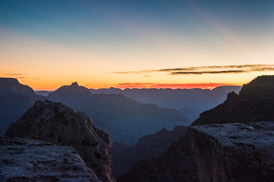 The sun illuminated the horizon and beamed across the sky, creating shafts of light flickering in the mile deep canyon below the Southern Rim.