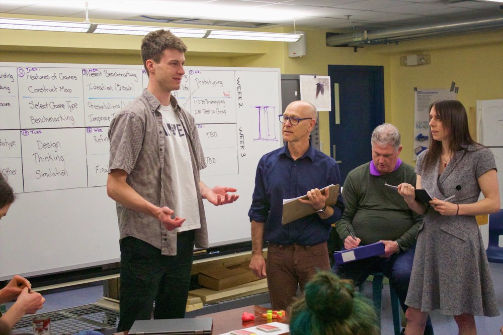 Colin MacIntosh presents his idea for a new board game to the instructors of the IDEA Sandbox boot camp.
