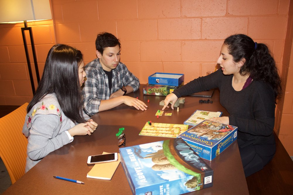 "Nour Houdeib, right, explains to her group members the instructions to the board game ""Above and Below"", while at the Board Room Cafe on May 7th."