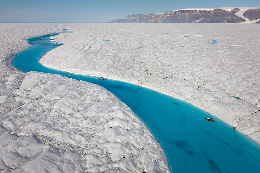 A vivid blue meltwater ravine running through the surface of Petermann Glacier on Greenland