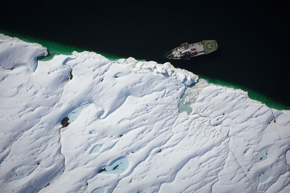 Ship at a glacier's edge photographed from the air