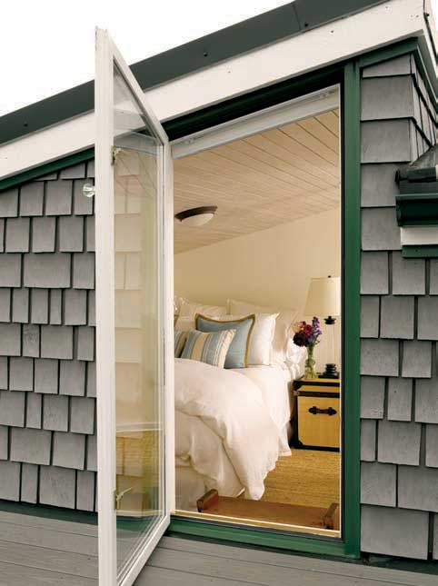 A WINDOW FROM THE LOFT BEDROOM OPENS ONTO A ROOFTOP DECK.