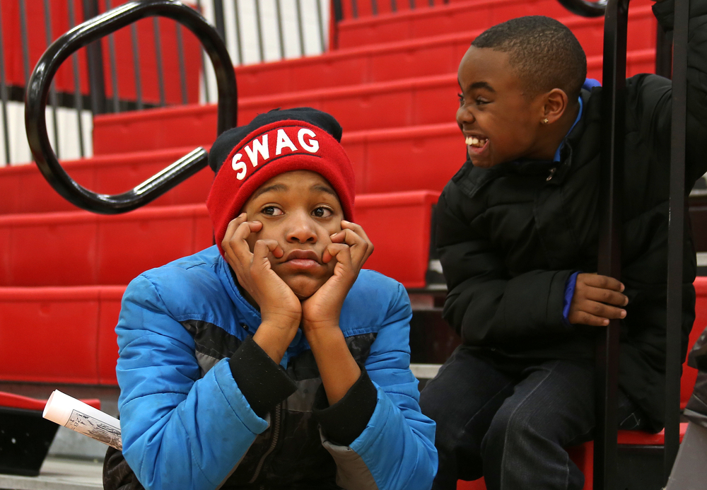 Muskegon Heights Academy fans, Dajuan Garrett, 11, center, and Jamarion Diggs, 9, right, watch the North Muskegon team warm-up on the court before their Class C boys basketball district championship game against Muskegon Heigths at Kent City High School.