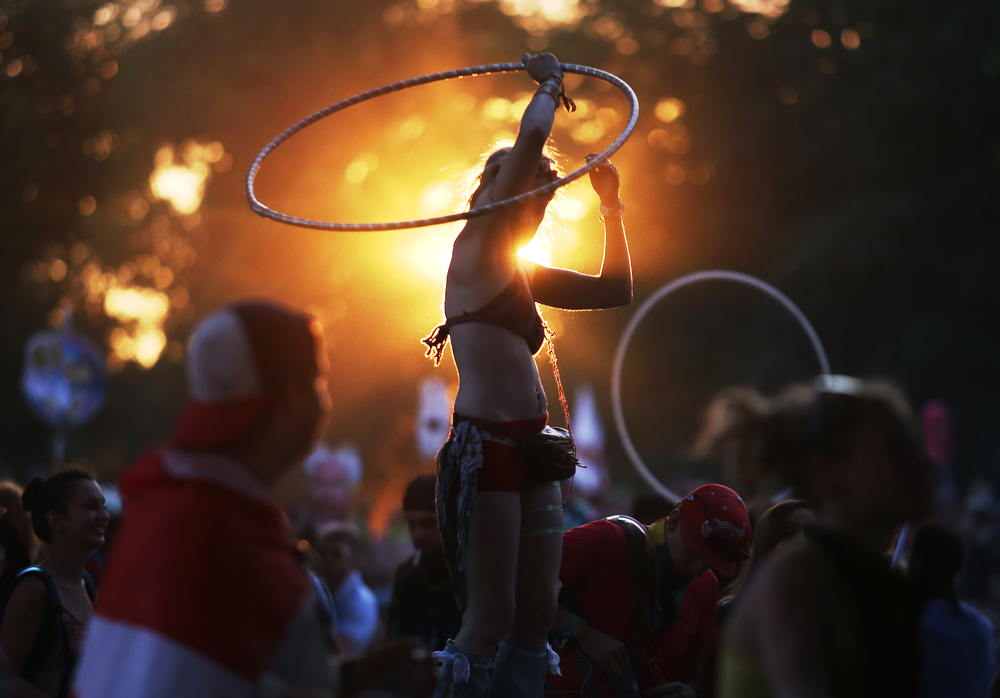 Ashley Landau of Chicago, Ill., center, moves with the rhythm and her hula hoop to The String Cheese Incident during their performance at Electric Forest's Ranch Arena in Rothbury, Mich. on Saturday, June 27, 2015.