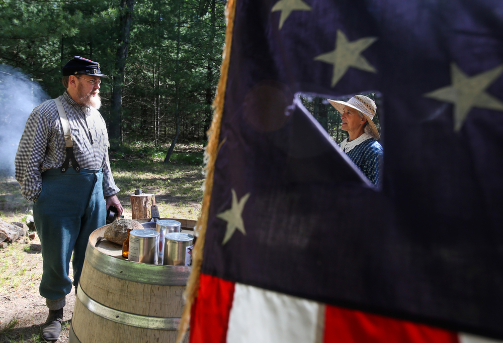From left, John Braden, a camp guard interpreter speaks with Constance Campagna, a United States sanitary commission worker on the grounds of a replica Civil War camp at the Michigan's Heritage Park on opening day of it's first season in Whitehall, Mich. on Saturday, June 6, 2015.