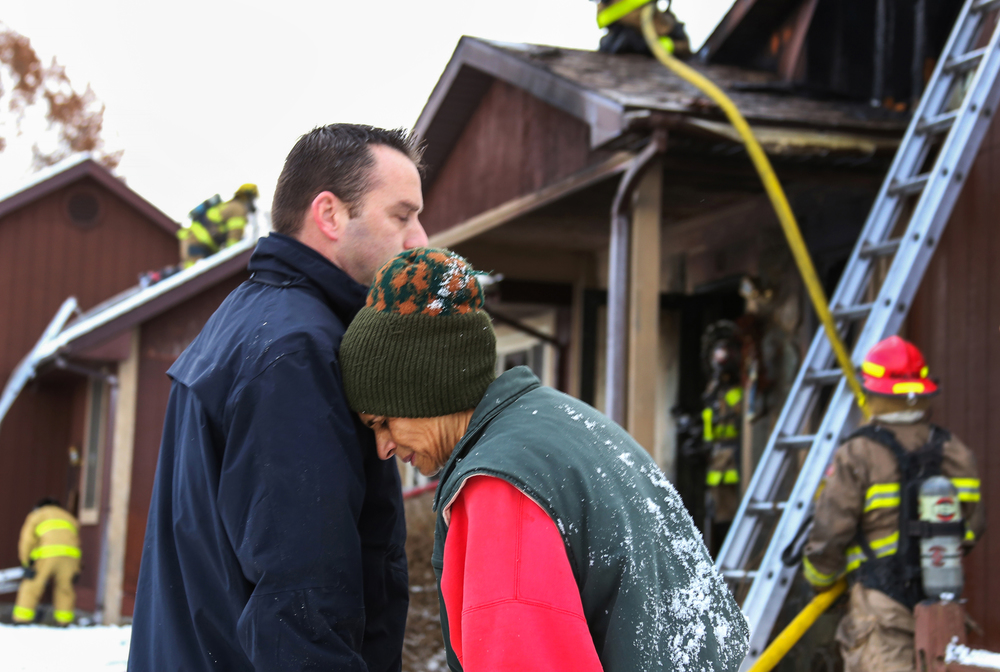"Lynn Edlund rests her head on the shoulder of Fruitport Township Deputy Fire Chief Brian Michelli outside of her rustic, one-story home as firefighters begin to control the blaze on South Brooks Road in Fruitport Township, Mich. on Nov. 13, 2014. Firefighters from several departments assisted Fruitport Township Fire Department with the fire that started in the chimney and quickly worked its way into the attic, devouring everything at the roof of the structure. ""I'm in shock,"" Edlund said. ""What do you… where are we going to live right now? All of our worldly possessions are in there."""