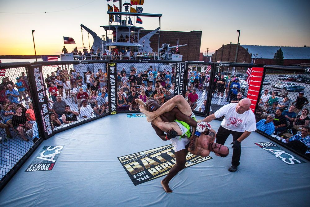 Desmond Colvin takes down Todd Roberts on Thursday, July 30, 2015 during a mixed martial arts match on the deck of the USS LST 393, a WWII transport ship docked in Muskegon, Mich. Roberts was taken away by ambulance after too many blows to the head.