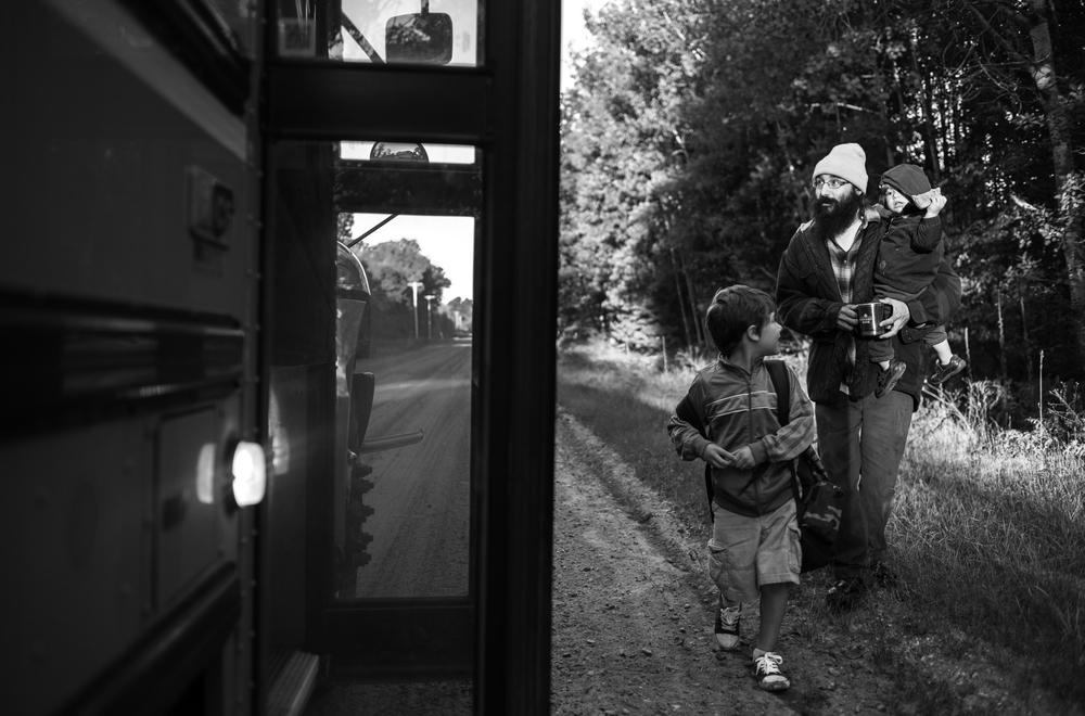 """After crossing the street in front of their """"small house"""" on the outskirts of the village of Sanford, Ben Cohen stands by as his son Elijah, 6, goes off to school. In the fall of 2013 Cohen made a lifestyle change when he quit his corporate job at State Farm to become a full-time farmer. With the help of his wife, Heather, they have created a simple style living."""