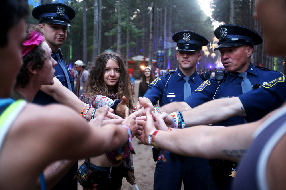 Michigan State police officers put their hands together with a group of festival goers in the Sherwood Forest during Electric Forest on Saturday, June 27, 2015.