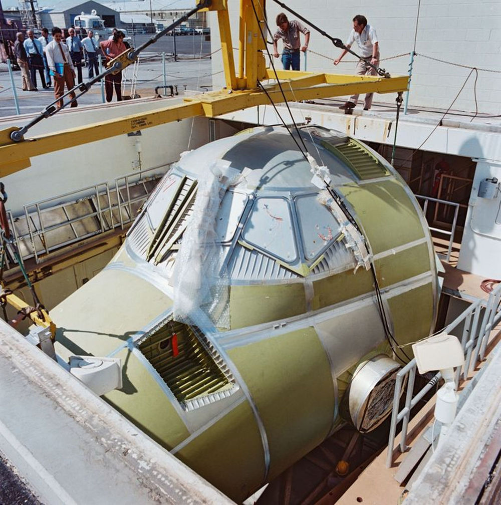 Atlantis' crew module is carefully installed into the vacuum chamber test cell at Rockwell's plant in this photo from March 31, 1983..jpg