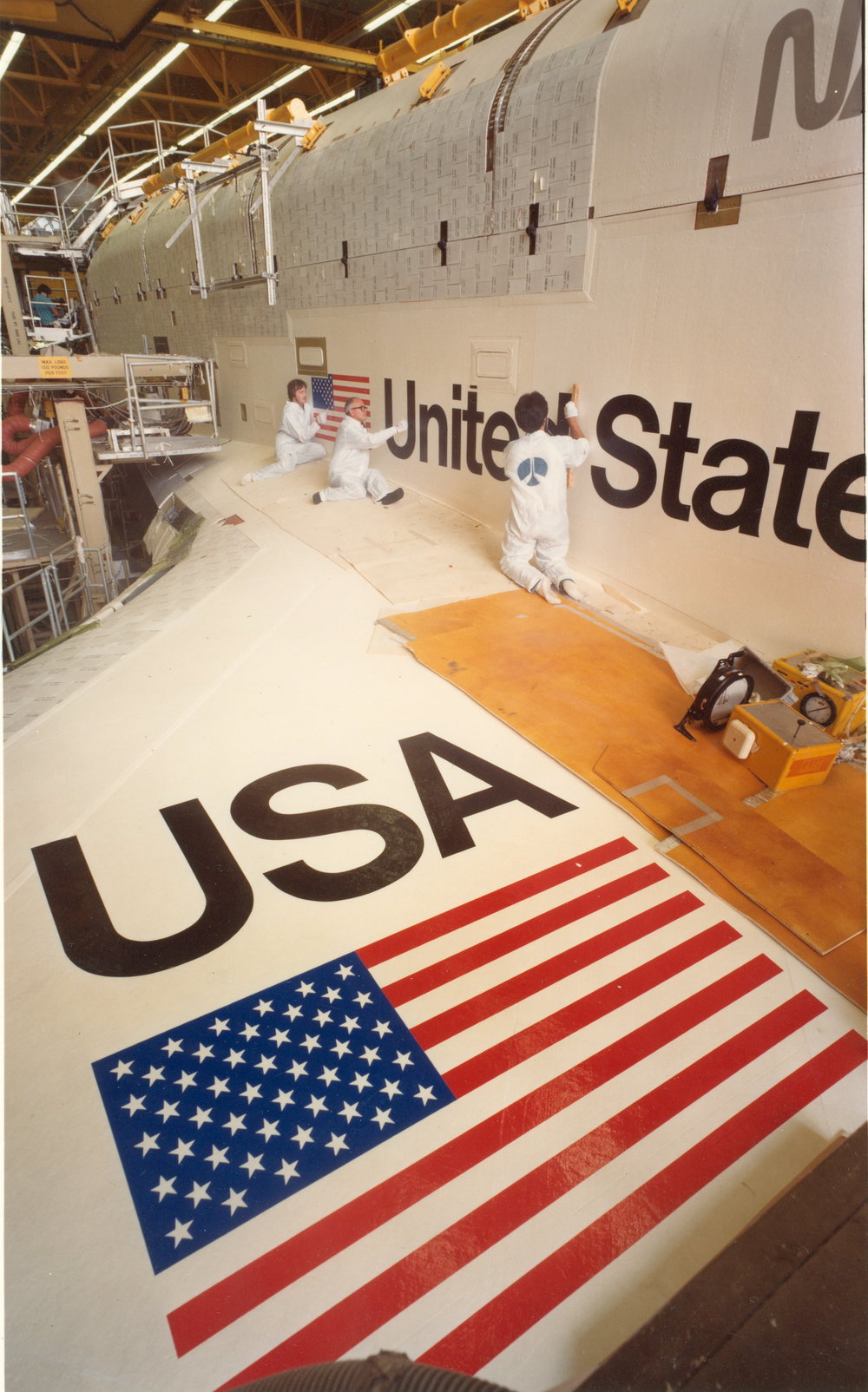 workers finish lettering and decals on shuttle at rockwell 001.jpg