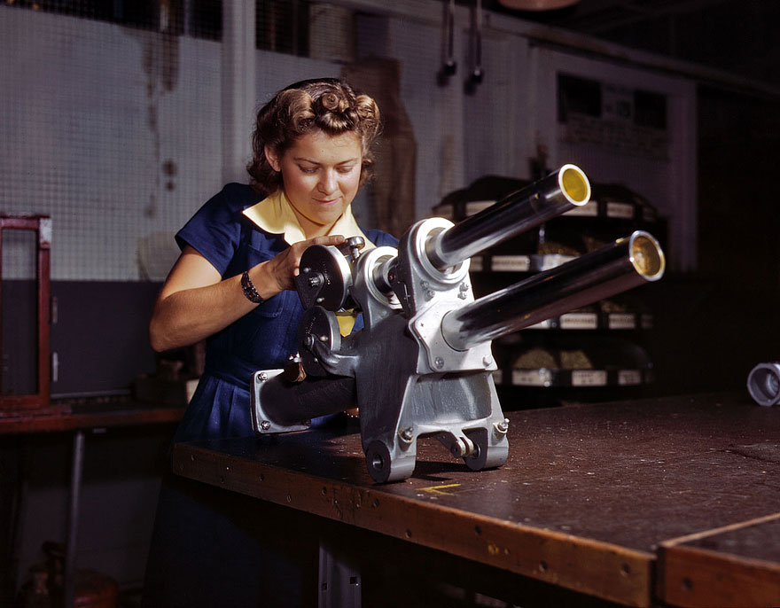 "October 1942. Inglewood, California. ""Young woman employee of North American Aviation working over the landing gear mechanism of a P-51 fighter plane."""