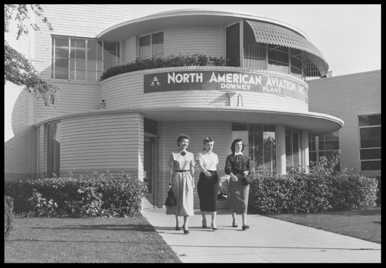 Photograph of female workers leaving the North American Aviation plant in  Downey . North American Aviation's Downey Plant is supplied by (left to right) Marion Burgman, Wilma McDonnell and Chari Sewell, company employees.  Image- USC Digital Archive