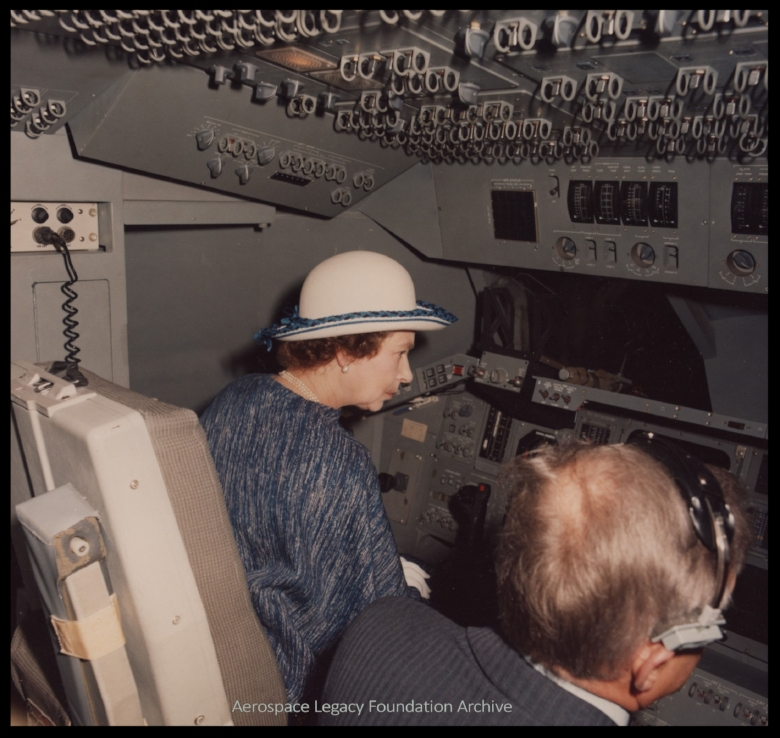 Queen Elizabeth visits Rockwell plant in Downey, 1980's. She is inside the Space Shuttle mock-up in the DEI Room, sitting with George Jeffs.  Image- Aerospace Legacy Foundation Archive.