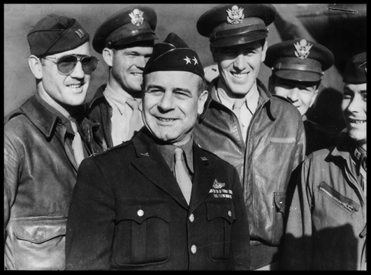 Lt. Gen. James H. Doolittle (center), commander of the Army Air Forces Eighth Air Force, is surrounded by a group of U.S. flyers. (This picture was taken before his promotion to lieutenant general.) The general took part in the first raid on Tokyo on April 18,1942, when a squadron took off from the USS Hornet in the North Pacific Ocean to bomb military installations in Japan. (U.S. Air Force photo)