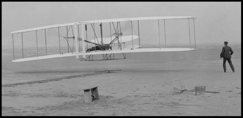 Orville takes off with Wilbur running beside, December 17, 1903. Wright Flyer in flight. Image- Wikipedia