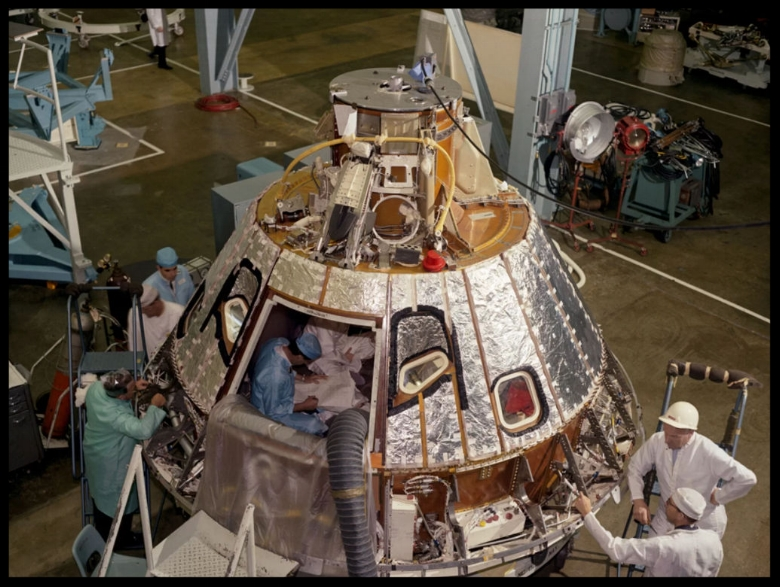This high angle view shows the Apollo spacecraft Command Module for the AS-204 mission (later renamed Apollo 1), looking toward -Z axis, during preparation for installation of the crew compartment heat shield, showing mechanics working on aft bay. Image- Space.com