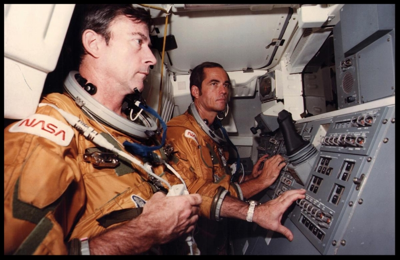 Looking aft toward the cargo bay of NASA's Space Shuttle Orbiter 102 vehicle, Columbia, Astronauts John Young (left) and Robert Crippen preview some of the intravehicular activity expected to take place during the orbiter's flight test, at Kennedy Space Center October 10, 1980.  Image NASA.  More here...