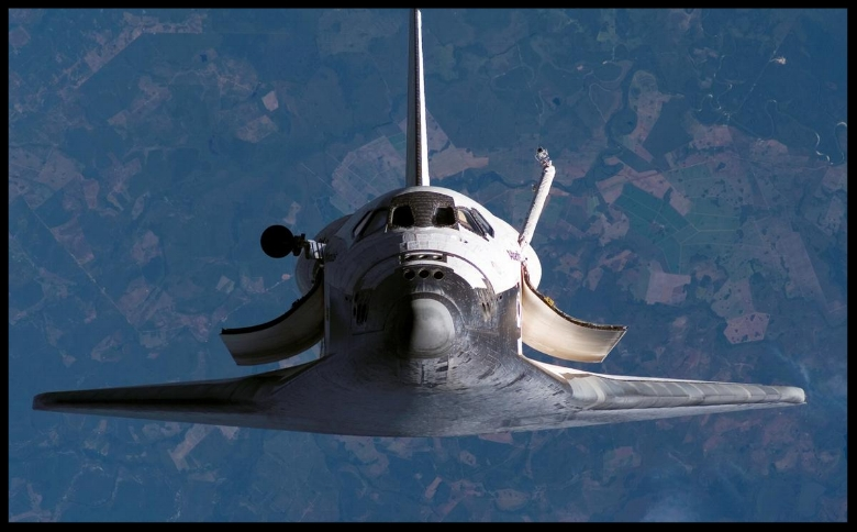 A view photographed from the International Space Station in 2007 shows the Space Shuttle Atlantis above the Earth, as the two spacecraft were nearing their link-up in Earth orbit.