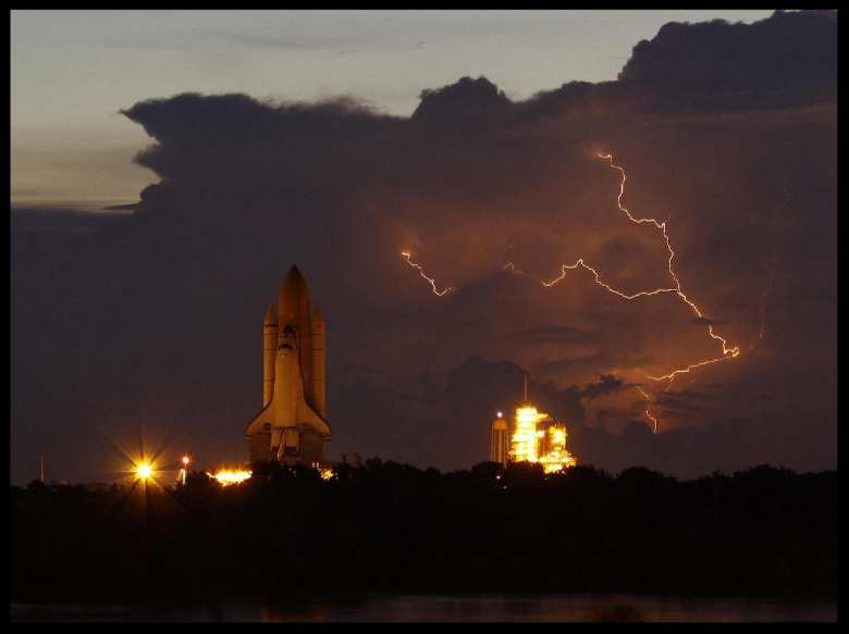 Rollout of space shuttle Discovery is slow-going due to the onset of lightning in the area of Launch Pad 39A at NASA's Kennedy Space Center in Florida, on August 4, 2009. The rollout was in preparation for launch on the STS-128 mission to the International Space Station