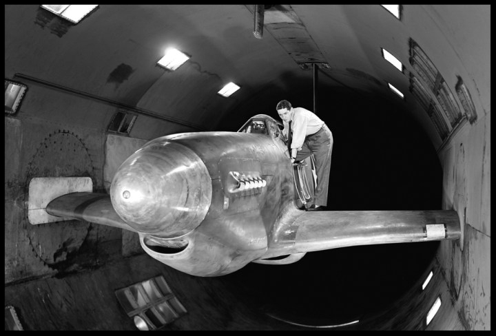 """By testing a North American XP-51B Mustang with cropped wings in the 16-foot High-Speed Tunnel, Ames researchers traced the source of a serious rumble to the location of the plane's radiator cooling scoop below the fuselage. The problem scoop is barely visible below the wing. Lowering it slightly moved it outside the turbulent boundary layer and eliminated the rumble. Note the turntables in the walls for pitch adjustment"". NASA image.    More here..."