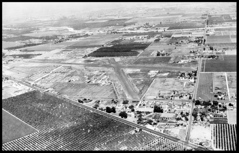 Aerial view Vultee Field/ Consolidated Vultee Downey plant, c1944 in full camouflage.  Surrounded by Lakewood Blvd., Imperial Hwy., Bellflower Blvd.with the San Gabriel River in the distance. Santa Fe Springs oil well at the very top. Image- Historic American Buildings Survey Downey NASA Plant.