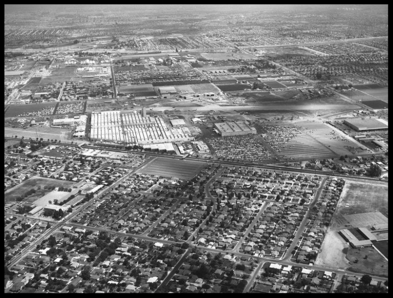 North American Aviation Space & Information Division (S&ID) in Downey, California looking east between Lakewood Blvd. and Bellflower Blvd.; Stewart & Gray Road and Imperial Highway. 1960's. Alameda Elementary School is on the lower right. Lakewood Blvd. runs through the center of photo crossing Stewart & Gray Road on the left and Imperial Highway (out of view) on the right. The San Gabriel River can be seen in the distance crossing the image. and the border of Downey and Norwalk, Ca.  Image- LAPL