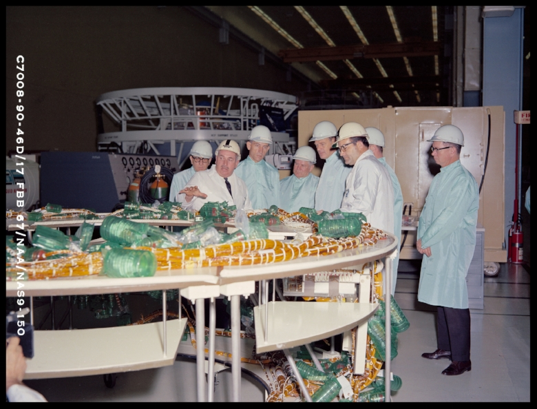 Above-  Congressman Earle Cabell and other members of the United States House Subcommittee on Manned Space Flight inspecting a main crew compartment wire harness during a tour of the High Bay Clean Room Facility. NAA, DOWNEY, CA 1967