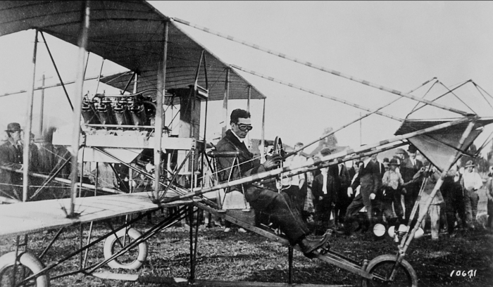 Glenn L. Martin in pusher-biplane. Note the newspapers stacked on wing. Martin delivered newspapers from Fresno to Madera as a part of his promotional efforts to fund first plant. Photo circa 1912