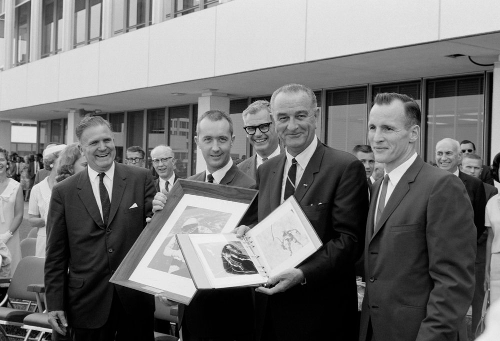 President Lyndon B. Johnson holds a Gemini-4 souvenir photo album
