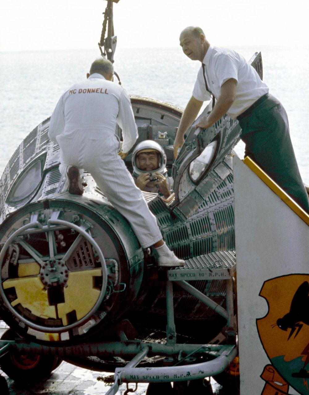 Astronaut Walter H. Schirra Jr. (on right), Command pilot, climbs from his Gemini VI spacecraft as he and Astronaut Thomas P. Stafford (not in view) arrive aboard the aircraft carrier U.S.S. Wasp