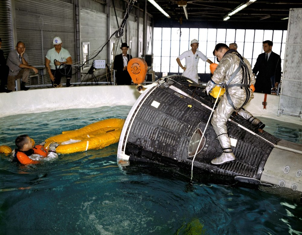 Astronauts John Young and Virgil I. (Gus) Grissom are pictured during water egress training in a large indoor pool at Ellington Air Force Base, Texas. 1965