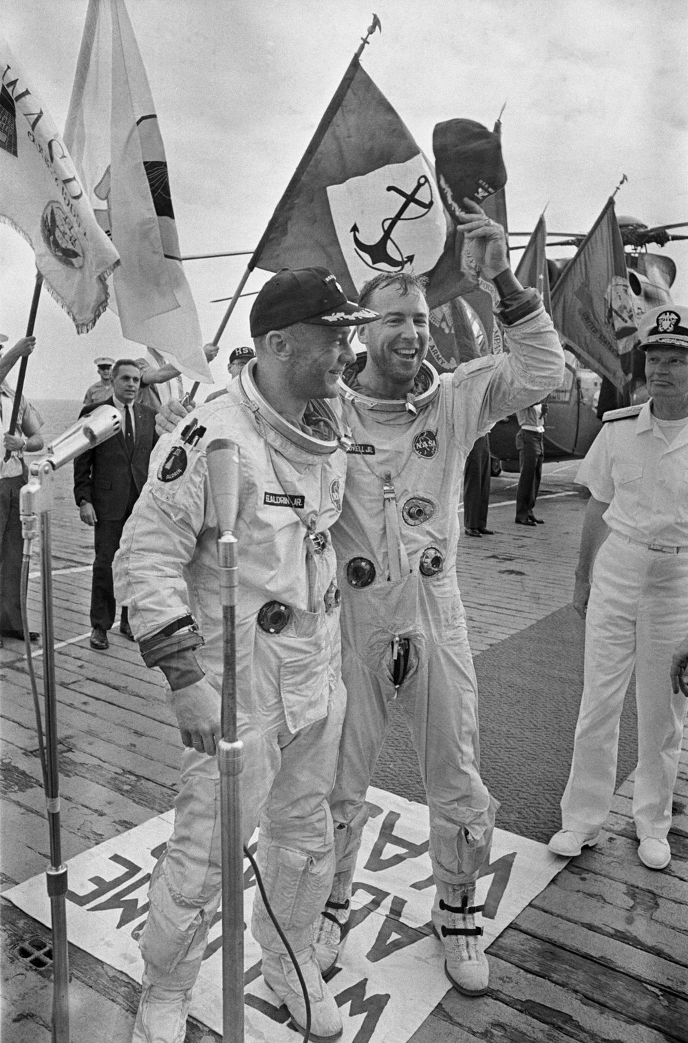 Astronauts James A. Lovell, Jr., and Edwin E. Aldrin, Jr., are welcomed aboard the aircraft carrier, USS Wasp 1966