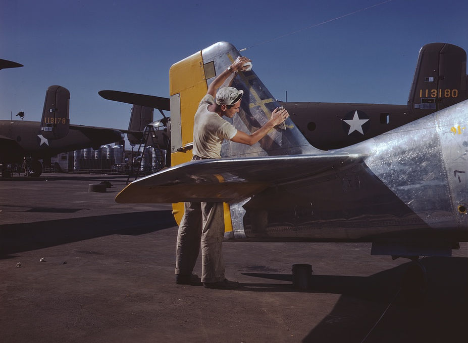 On North American's outdoor assembly line, a painter cleans the tail section of a P-51 fighter prior to spraying the olive-drab camouflage of the U.S. Army, NAA, Inc., Inglewood, Calif.
