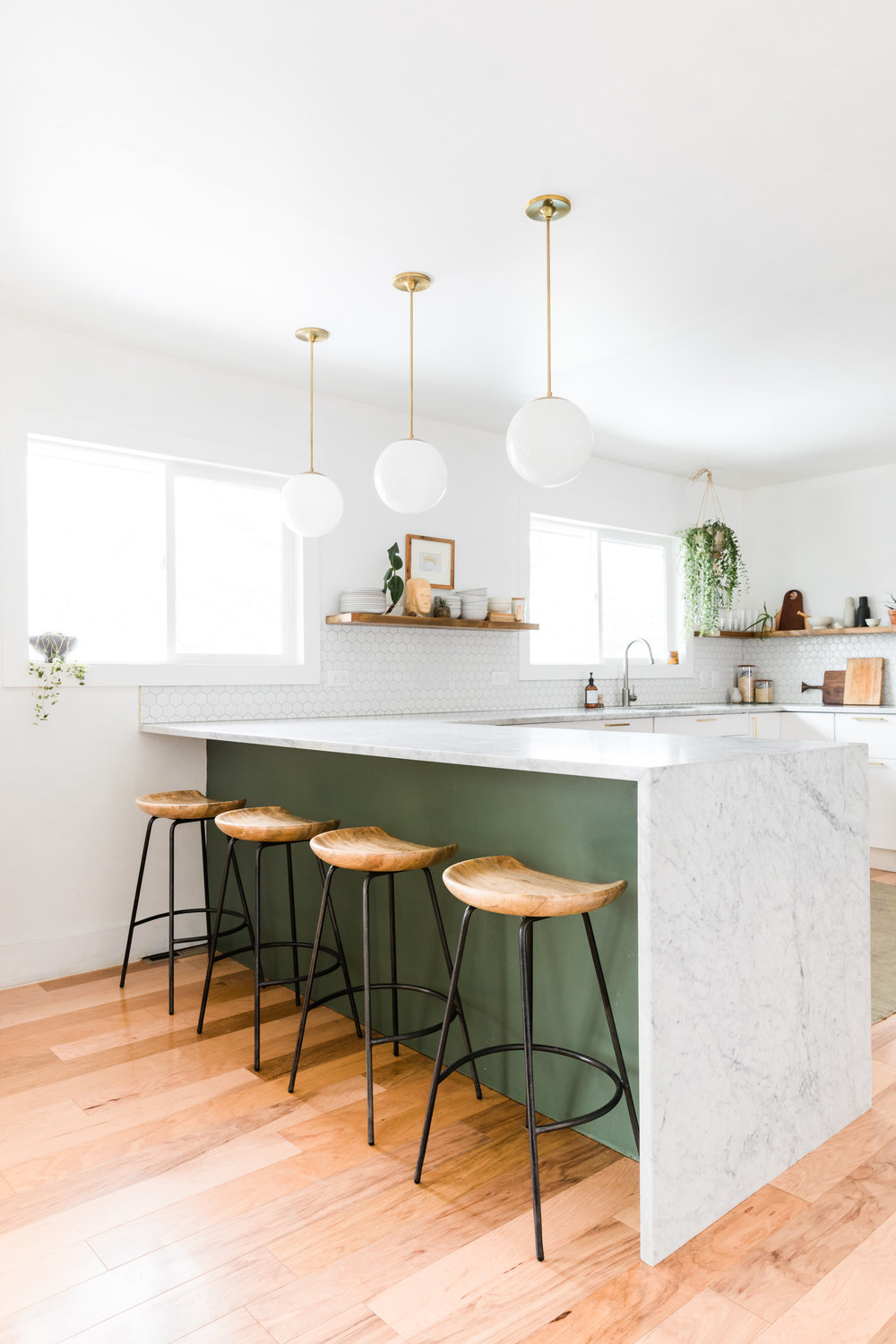 Green and white minimalist kitchen with marble waterfall counters and wood-topped stools.