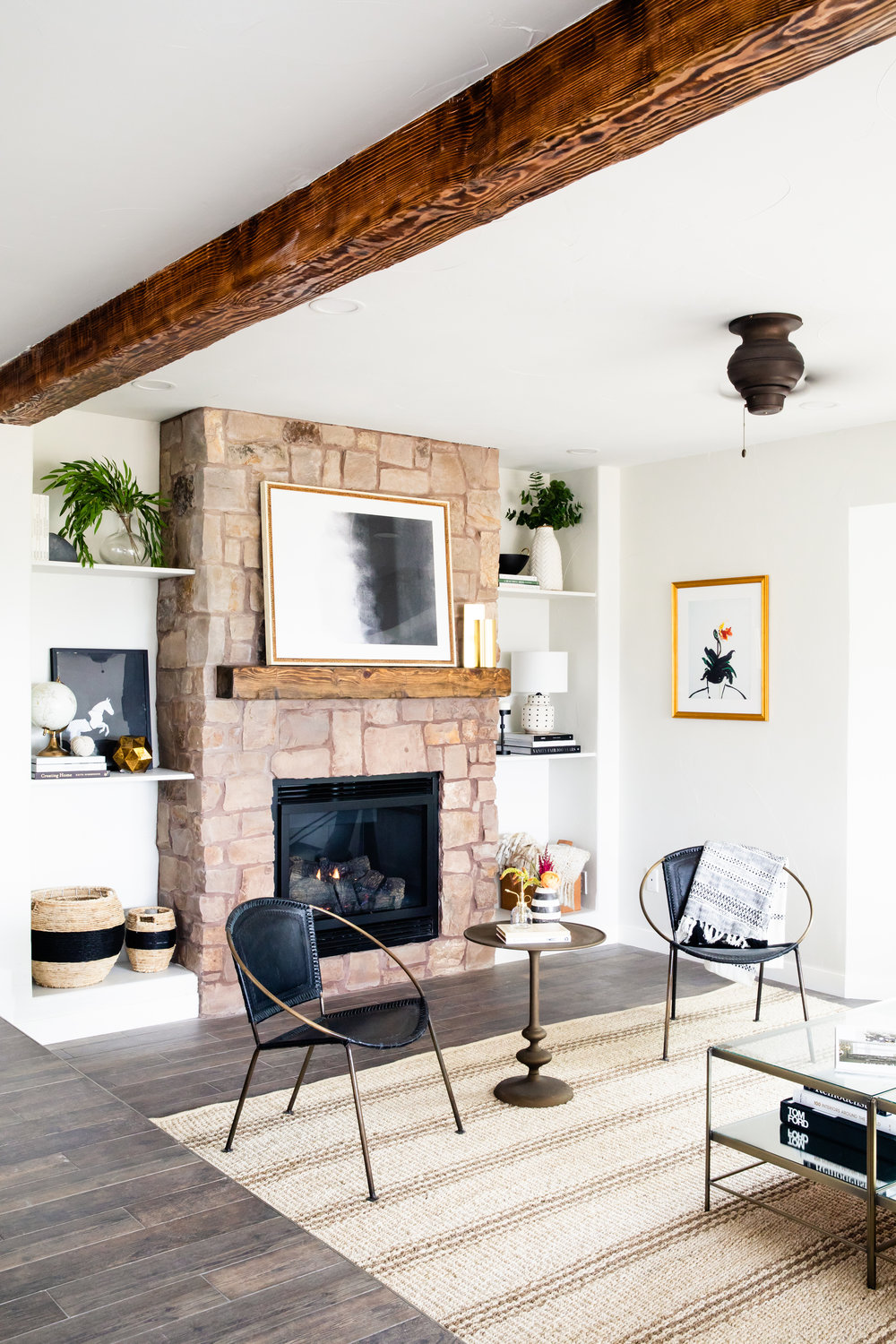 HGTV home renovation for new pilot show in modern, rustic feel with wooden beam, stone fireplace, plants, and modern artwork.