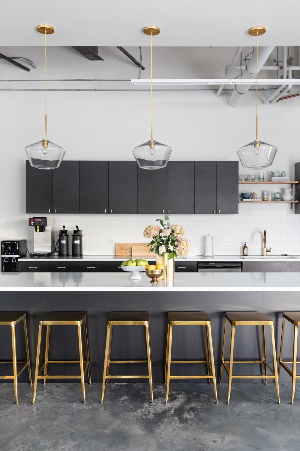 Black and white modern kitchen with marble counters and brass stools.