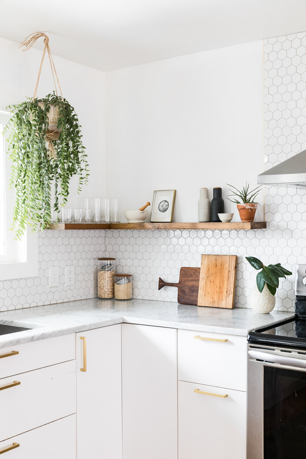 Minimalist kitchen with hanging plant, wooden floating shelf, and marble countertops.