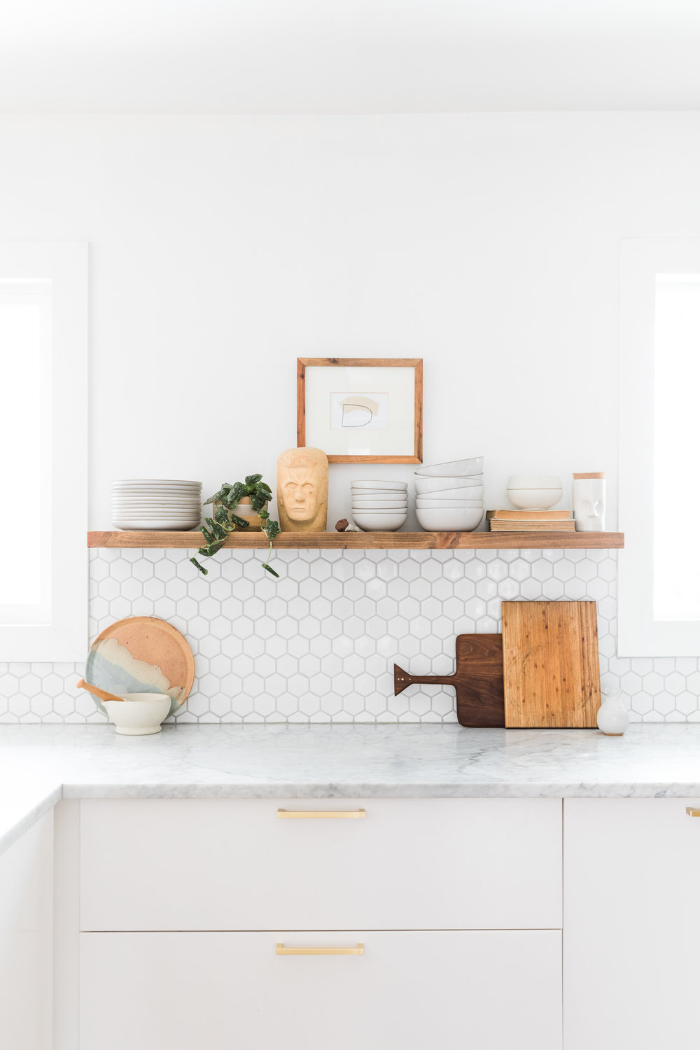 White kitchen with wooden floating shelves and marble countertops.