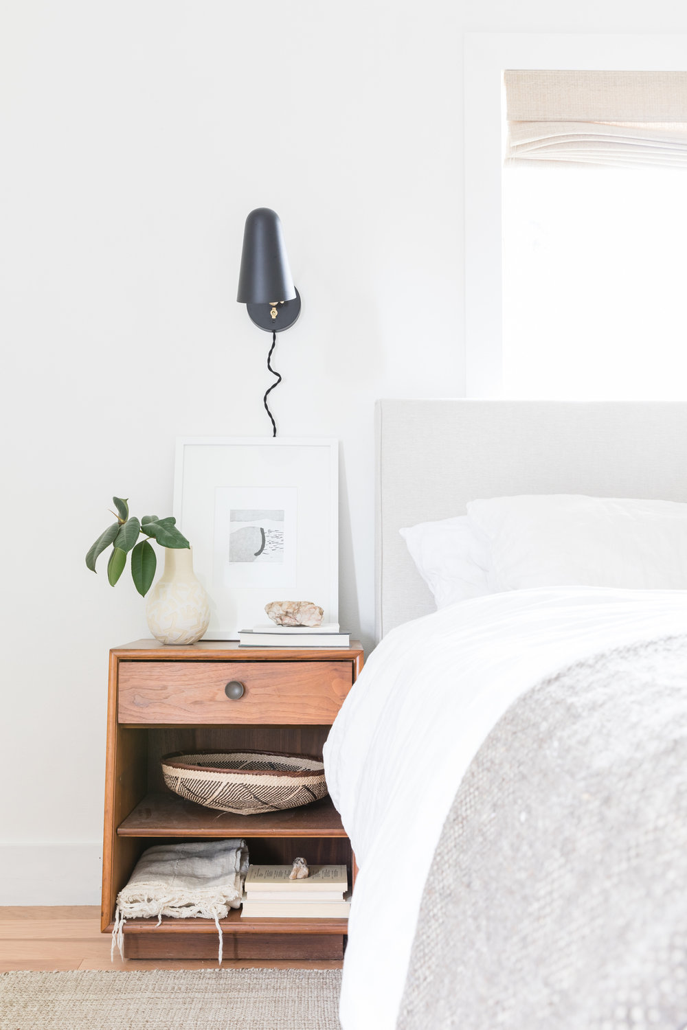 White-walled bedroom with linen bedding and black wall sconce.