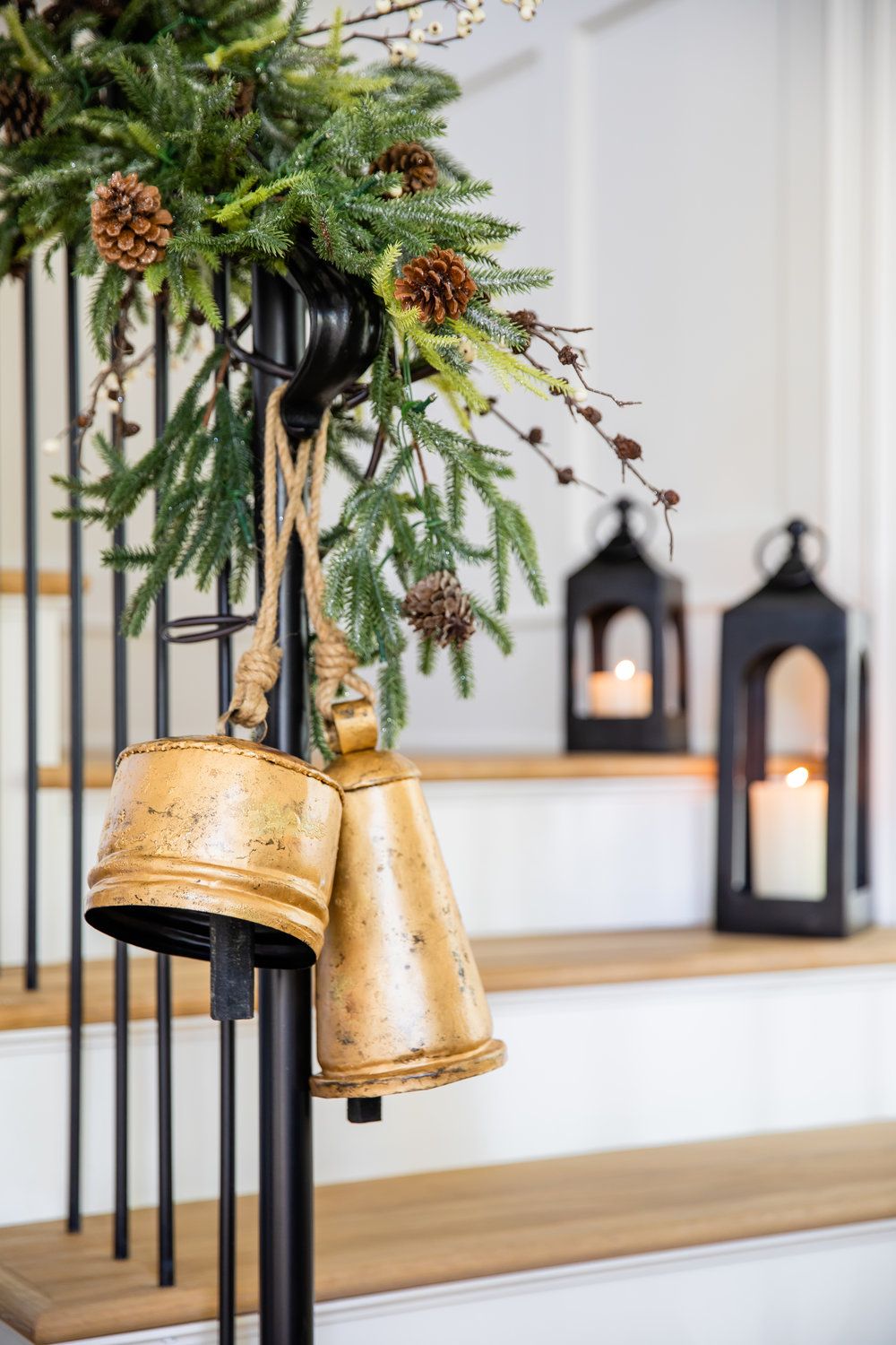 Pottery Barn brass Christmas bells and lanterns on staircase.