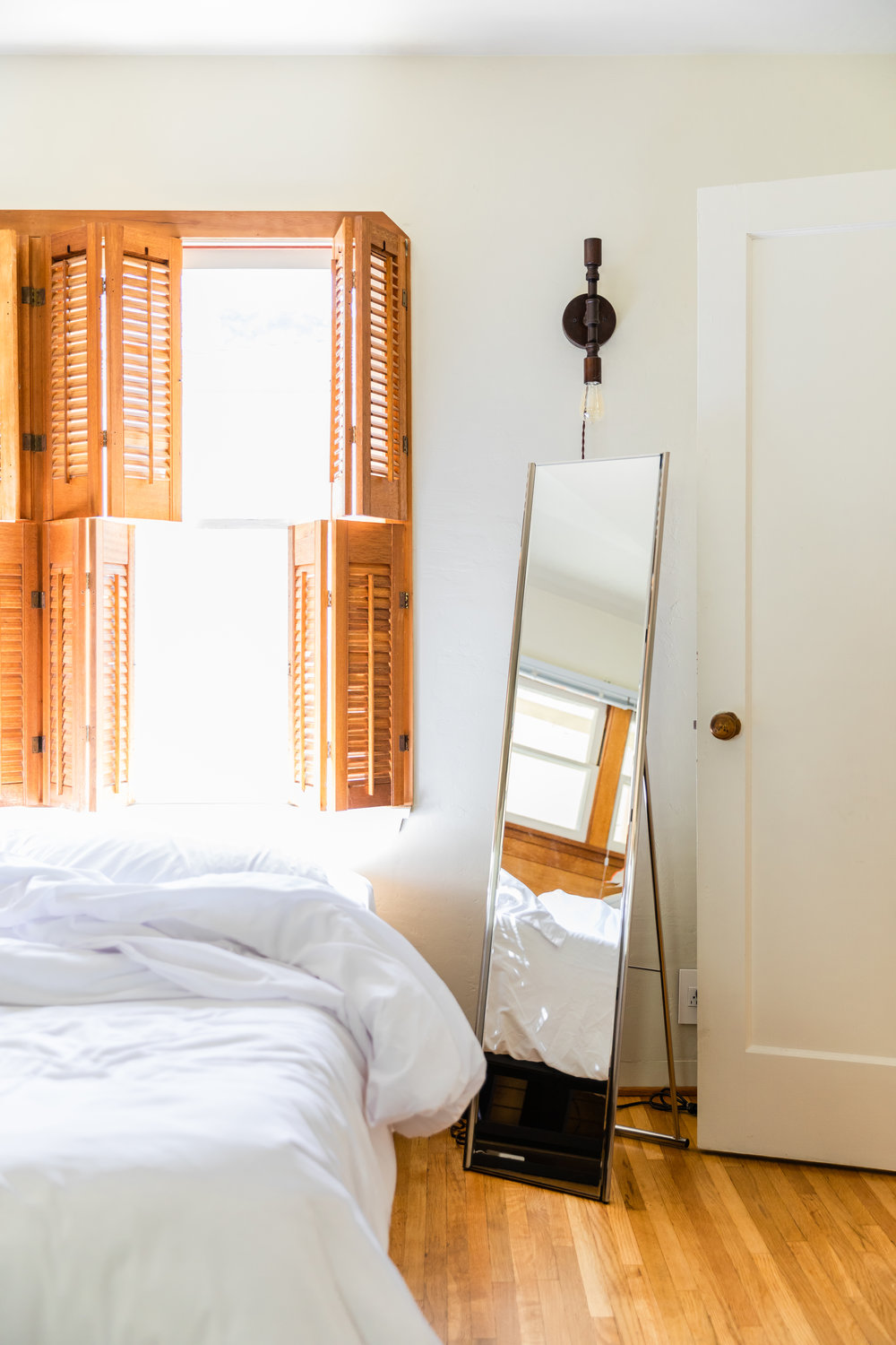 Los Angeles Airbnb with white walls and white bedding and sunlight streaming in through wooden shutters.
