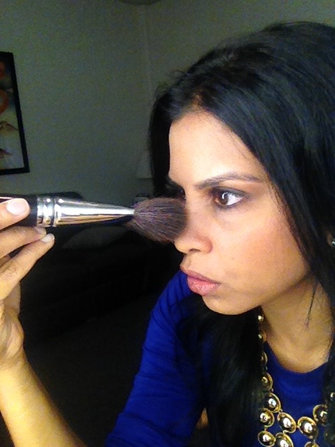 Hitha Herzog applying her own makeup with a blush makeup brush, clearly loving every second of it!