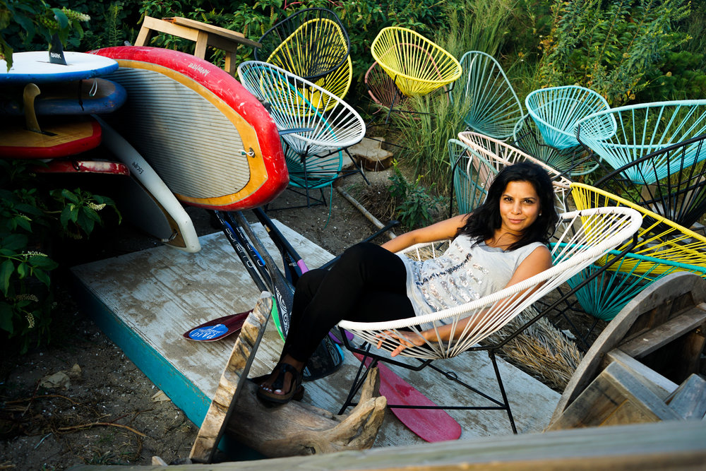 Hitha Herzog surrounded by surf boards and geometric chairs, lounging.