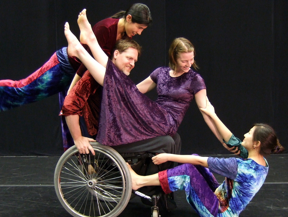 Image: Four mixed ability dancers of different ethnicities are performing.  Each is wearing a colorful velour costume.  One dancer sits in a wheelchair, another sits on his lap, and a third reclines on the floor.  Another dancer stands behind the wheelchair user.  thy are all smiling and in close contact. PHOTO CREDIT:  Sean Sullivan