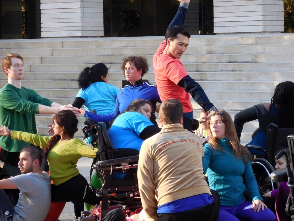 Image: a large group of mixed ability dancers performs outdoors.